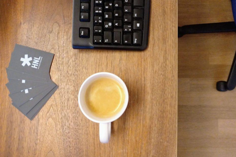Schreibtisch mit Tastatur, Kaffee und Visitenkarten von HNL Physiotherapie