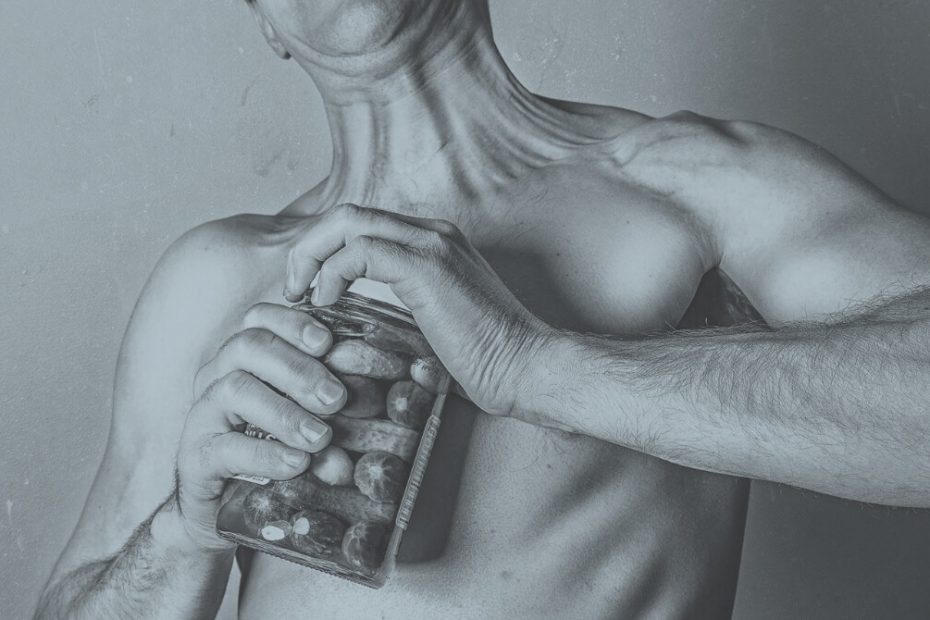 Mann öffnet Gurkenglas mit zu schwachen Muskeln